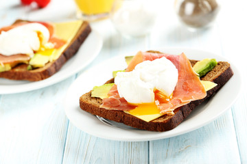 Poached eggs with avocado and bacon on toasts on blue wooden tab