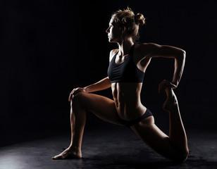 Sport fitness woman doing yoga on black background