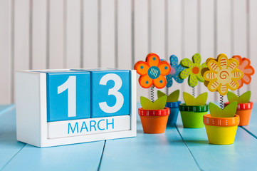 March 13th. Image of march 13 wooden color calendar with flower on white background.  Spring day, empty space for text