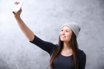 Young girl in hat taking photo of her self with smart phone on grey wall background