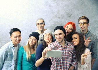 Young people taking group photo with smart phone on grey wall background