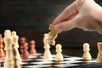 Female hand playing chess on wooden background