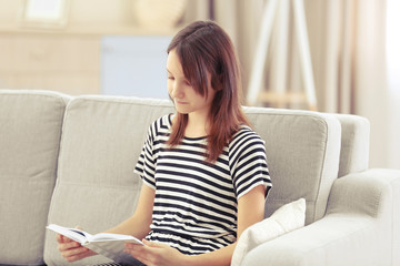 Beautiful girl reading book on sofa, indoor