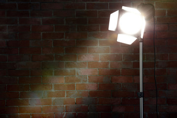 Studio light flash on brick wall background