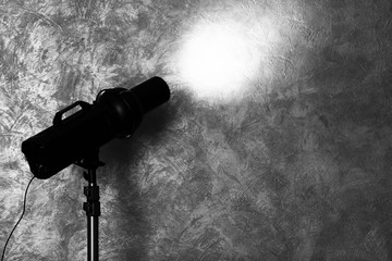 Studio light flash on wall grey textured background