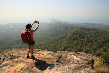 young woman backpacker taking photo with camera on mountain peak