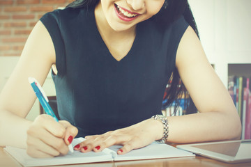 Beautiful woman smiling and writing a notebook on table (Focus on her mouth)