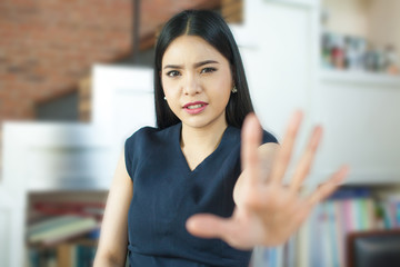 Asian woman with her hand signaling stop (only face is in focus)