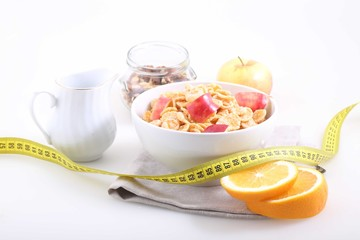 Muesli with Apple slices, an orange and the measuring tape, a us