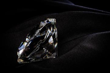 Beautiful diamond with reflection on black fabric