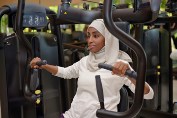 Young arab muslim woman wroking out in a Gym
