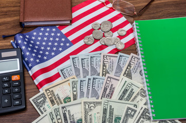 usa flag with dollar bills and coins, calculator, notepad on table