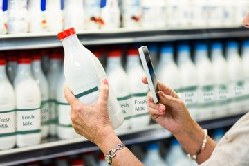 Close up of senior woman taking picture of milk bottle