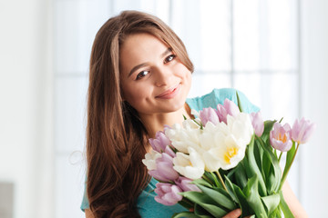 Pretty cheerful young woman with bouquet of flowers