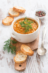tomato soup with rice and vegetables in a saucepan and bread