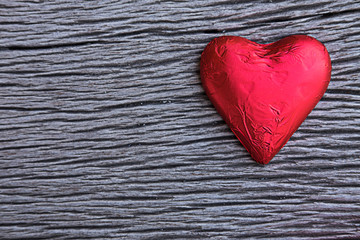 Red Heart chocolate on wood Background
