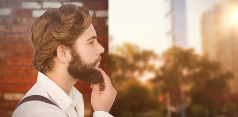 Composite image of profile view of hipster touching beard