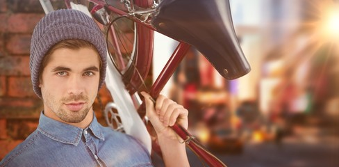 Composite image of portrait of hipster carrying bicycle