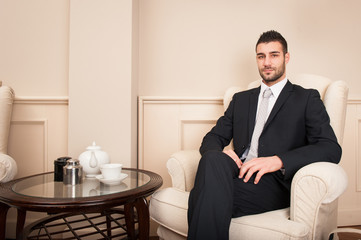 Confident young businessman portrait sit on armchair inside luxury hotel.