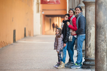 Happy family posing in the city of Bologna, Italy.