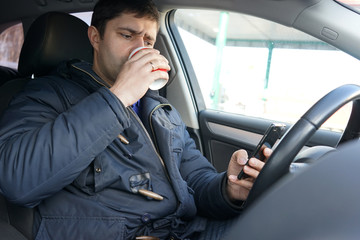 Young man drinking coffee  and looking at smartphone in the car