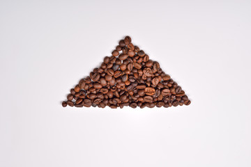 Triangle shape of roasted coffee beans on white background. Love
