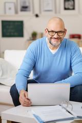älterer mann arbeitet zuhause mit laptop und unterlagen