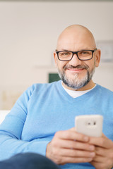 mann hält sein smartphone in der hand und schaut in die kamera