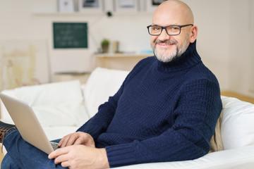 moderner älterer mann mit laptop auf dem sofa