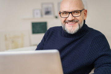 lächelnder älterer mann mit brille arbeitet zuhause am notebook