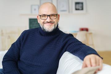 mann mit brille sitzt auf dem sofa im wohnzimmer