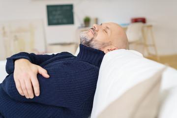 zufriedener mann liegt auf dem sofa und ruht sich aus