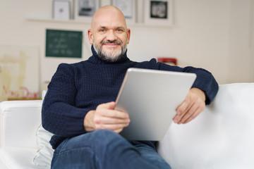 entspannter älterer mann sitzt auf dem sofa mit tablet