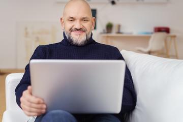 kreativer älterer mann mit laptop auf dem sofa