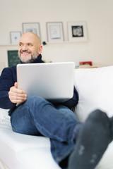 entspannter älterer mann sitzt auf dem sofa mit notebook