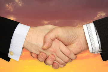 Businessmen shaking hands on a background of cloudy Sky