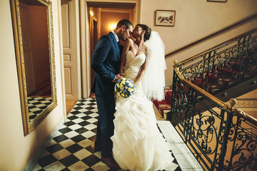 groom is kissing bride shoulder on the  background corridor with