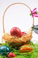 Easter eggs in wicker basket on white