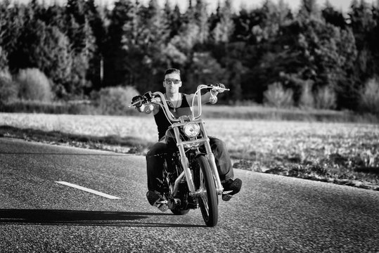 Tough, tattooed biker with his chopper in motion on the road