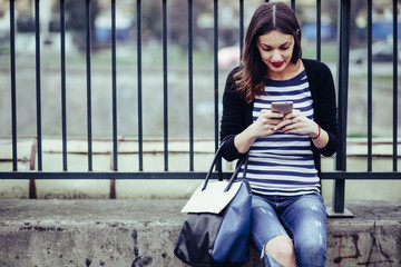 beautiful young woman looking at smart phone in city/ young smiling woman looking at her smartphone