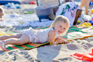 little blond girl is lying on the beach