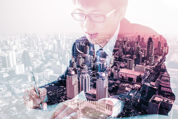 Double exposure of Business man signing a contract and city