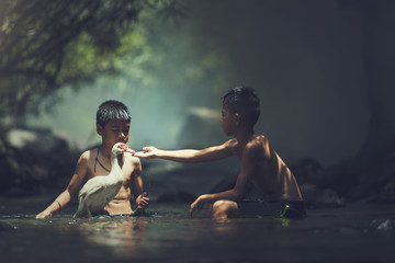 the two boys playing with white duck
