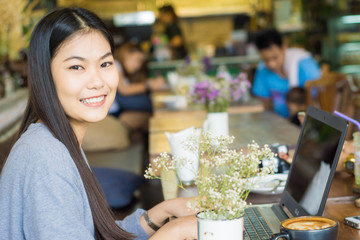 Beautiful asian woman using laptop inside coffee shop