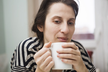the woman with a mug has tea in the room