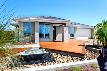 Modern house with trees and stone decoration items including a s