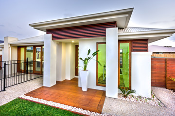 Modern house entrance with a wooden and concrete yard with a law
