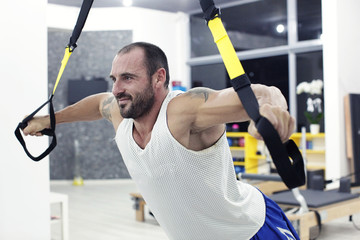 muscular man working in gym with special sport equipment
