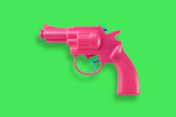 Pink water-gun on green background