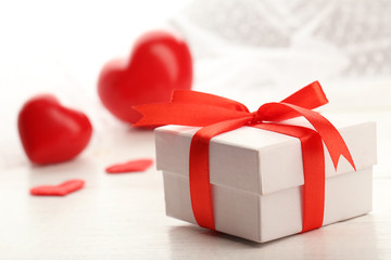 Gift box and decorative hearts on light wooden background